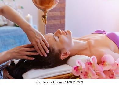 Caucasian woman having Ayurveda shirodhara treatment