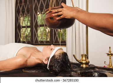Caucasian woman having Ayurveda shirodhara treatment in India