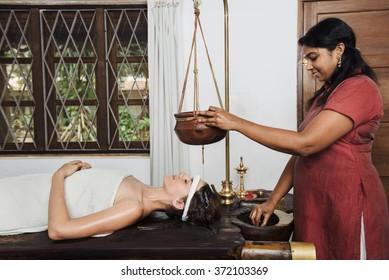 Caucasian woman having Ayurveda shirodhara treatment in India, Kerala state
