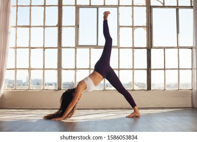 Caucasian woman in her 20s doing downward facing dog split. Young active woman practicing yoga by large open window in urban space