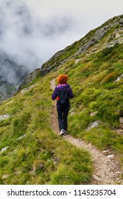 Caucasian woman hiker with backpack walking a trail in rocky mountains