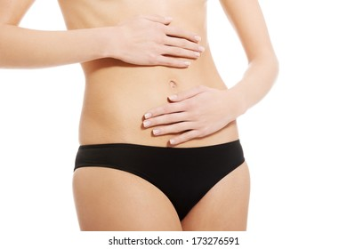 Caucasian woman is holding hand on her perfect flat belly. Isolated on white.