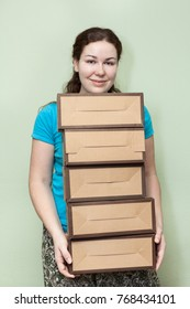 Caucasian woman holding several cardboard boxes in hands, removal into a house