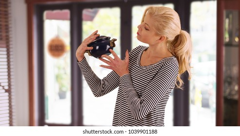 Caucasian woman looking at antique pot checking price tag inside store smiling