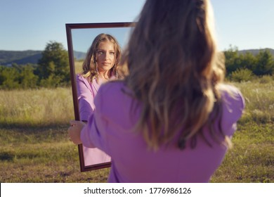 Caucasian woman looking herself in the mirror while standing in the field in sunny day - beautiful female hold mirror in front of her face outdoor in nature - mother nature identity concept