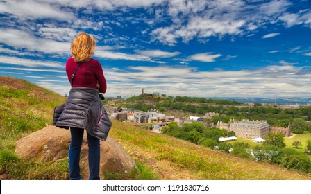 Caucasian woman looking out on Edinburgh from the cliffs of Holyrood Park on a bright sunny day with a blue sky and white clouds