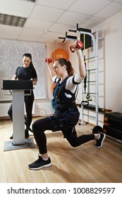 Caucasian woman makes exercises with weights in gym. Female trainer standing aside manages electric muscle stimulation purposed to increase effectiveness of training. Vertical shot