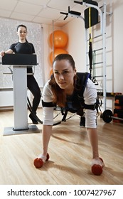 Caucasian woman makes push ups in gym. Female trainer standing aside manages electric muscle stimulation purposed to increase effectiveness of training. Vertical shot
