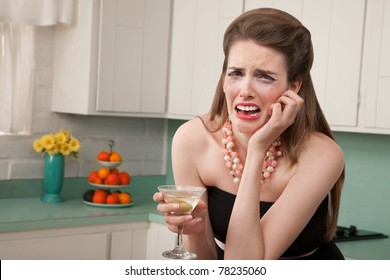Caucasian woman with a martini in her kitchen sobs
