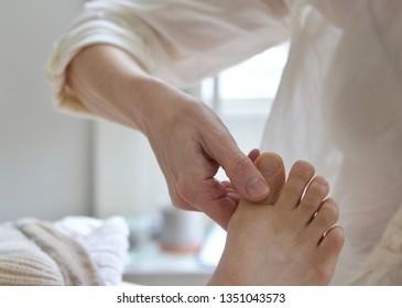 Caucasian woman massaging caucasian womans foot