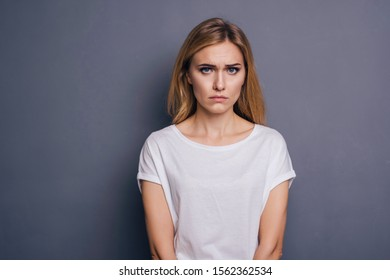 Caucasian woman in neutral casual outfit standing on a neutral grey background. Portrait with emotions: angry, pain, sickness and despair