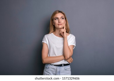 Caucasian woman in neutral casual outfit standing on a neutral grey background. Portrait with emotions: happiness, amazement, joy and satisfaction