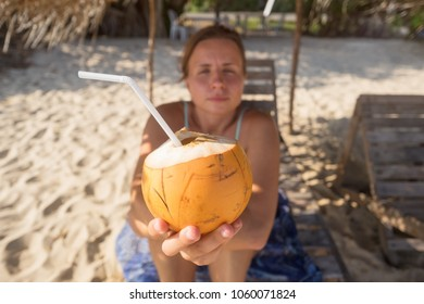 Caucasian woman offering cocnut to her friend. Delicious drink at the tropical beach
