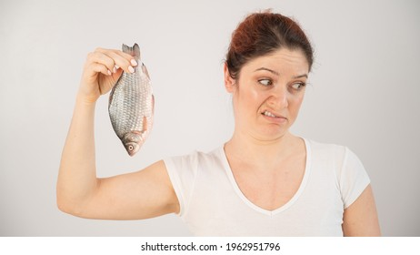 Caucasian woman opposes the disgusting smell of fish. A metaphor for women's health and intimate hygiene.