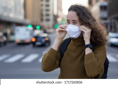 Caucasian woman out and about in the city streets during the day, putting on a face mask against covid19 coronavirus