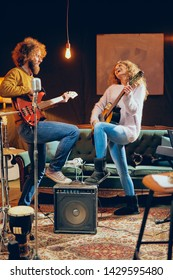 Caucasian woman playing acoustic guitar while man playing bass. Home studio interior.