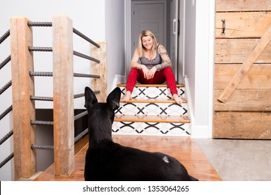 caucasian woman playing with her pinscher dog in the house