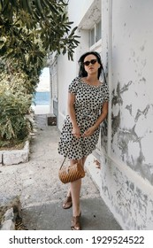A Caucasian woman in a polka-dotted flowy dress and sunglasses leaning against the wall