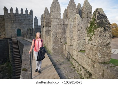 Caucasian woman posing in front of medieval gothic defensive walls Guimarães castle in Portugal on sunny day