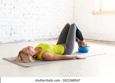 Caucasian woman practice pilates indoor. Start position for gluteal bridge with feet on small fit ball, selective focus. Workout, balance, fitness, trainer, recovery, healthy lifestyle concept.