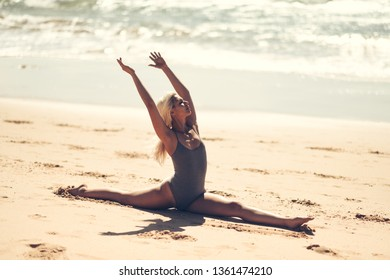 Caucasian woman practicing yoga at seashore. Young female doing fitness legs split on sand in the beach in Cadiz, Andalusia, Spain.