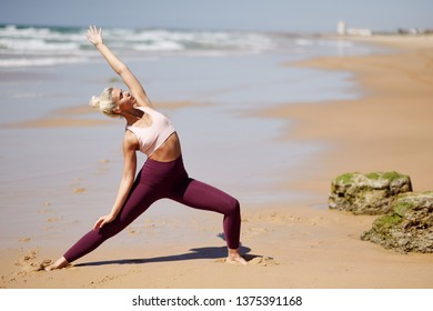 Caucasian woman practicing yoga at seashore. Young female raising arms in the beach in Cadiz, Andalusia, Spain.