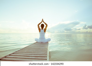 Caucasian woman practicing yoga at seashore - Shutterstock ID 142334290