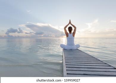 Caucasian woman practicing yoga at seashore - Shutterstock ID 159959027