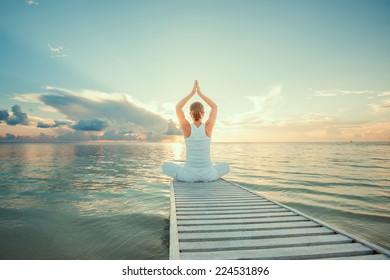Caucasian woman practicing yoga at seashore - Shutterstock ID 224531896