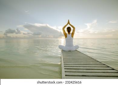 Caucasian woman practicing yoga at seashore - Shutterstock ID 232425616