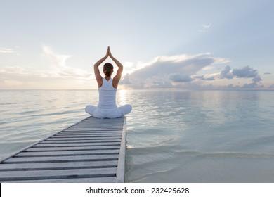 Caucasian woman practicing yoga at seashore - Shutterstock ID 232425628