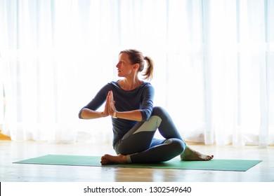 Caucasian woman is practicing yoga at studio