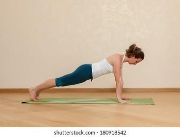 Caucasian woman is practicing yoga at studio (chaturanga dandasana)