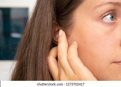 A caucasian woman pressing on her ear with her fingers