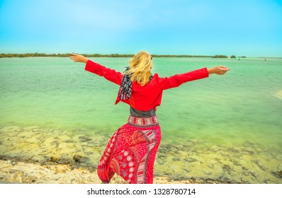 Caucasian woman with raised arms looking at the Al Thakira Mangroves Nature Reserve in Al Dhakira, a popular touristic attraction. Happy blonde tourist visits Qatar in Middle East, Persian Gulf.