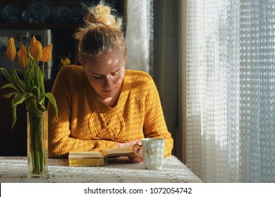 caucasian woman reading book and having tea at home