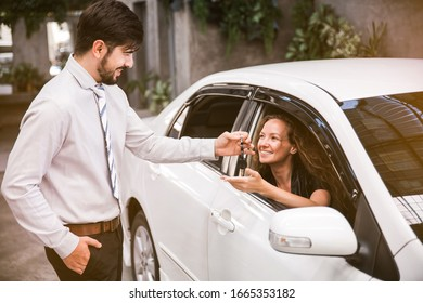 The Caucasian woman receiving car key with a smile from the Caucasian salesman. Auto Leasing Business. Auto dealership, Car dealership.