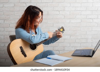 Caucasian woman remotely teaches guitar playing on laptop. Online music training