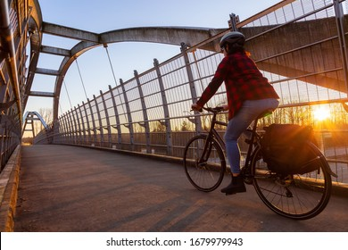 Caucasian Woman Riding a Bicycle on a Pedestrian Bridge over the Highway during a sunny sunset. Taken in Surrey, Vancouver, British Columbia, Canada.