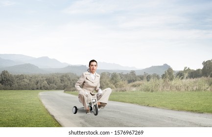 Caucasian woman riding kid's bicycle on asphalt road. Young employee in white business suit biking outdoor. metaphor of ineffective and incompetent work. Beginner level concept with bicyclist.