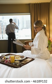 Caucasian woman in a robe sits on a hotel bed while reading the newspaper. A man stands in the background talking on his mobile phone. Vertical shot.