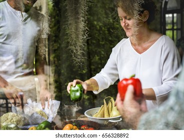 A caucasian woman selecting a bell pepper