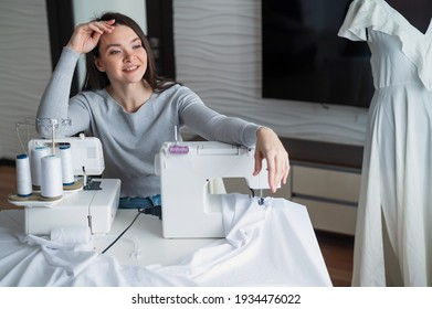 Caucasian woman sews a dress at home. Workspace of a seamstress