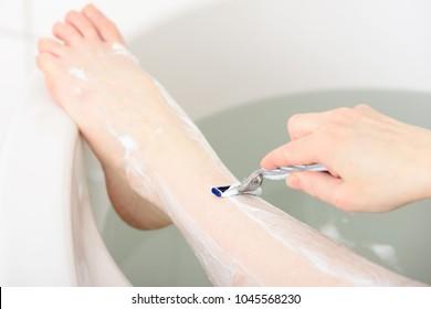 Caucasian woman shaving her leg in her bathtub. Detail of leg being shaved.