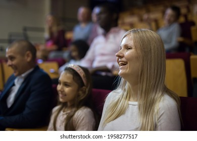 caucasian woman sitting at funny perfomance in theatrical auditorium