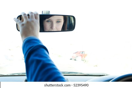 Caucasian woman sitting on driver's seat and looking in the rear-view mirror