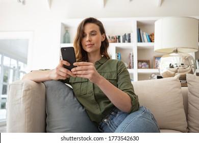 Una mujer caucásica pasa tiempo en casa, sentada en el sofá, usando su smartphone. El estilo de vida en el aislamiento domiciliario, el distanciamiento social en el bloqueo de cuarentena durante el coronavirus conforman 19 pandemias.