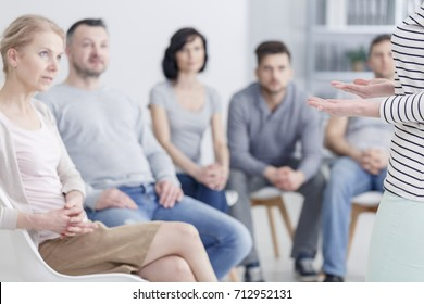Caucasian woman talking to group of people during sharing session