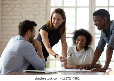 Caucasian woman team leader mentor teach staff multiethnic workers at corporate group briefing explain work results analyzing financial report together, planning project, brainstorming process concept