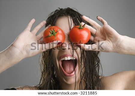 Caucasian woman with tomatoes covering her eyes.